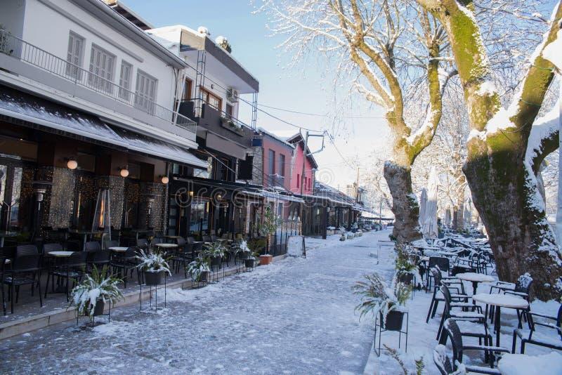 Kaffeegeschäfts-Tabellenstühle in der Schneeeiswintersaison-Baumstraße in Ioannina-Stadt Griechenland lizenzfreie stockfotografie