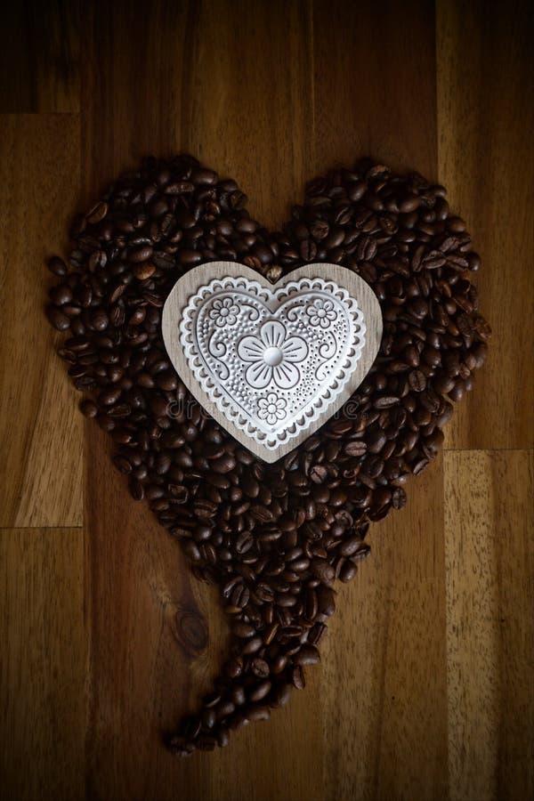 Kaffeeherz auf hölzernem Schreibtisch lizenzfreies stockfoto