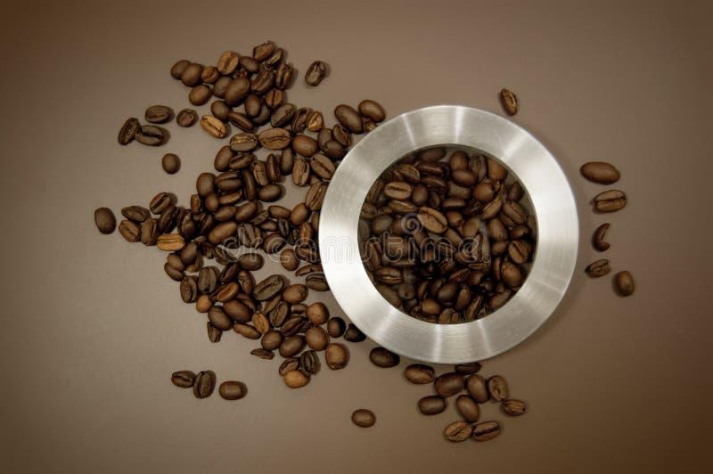 Kaffeekanisterdeckel und Kaffeebohnen auf dem Tisch zerstreut stockfotos