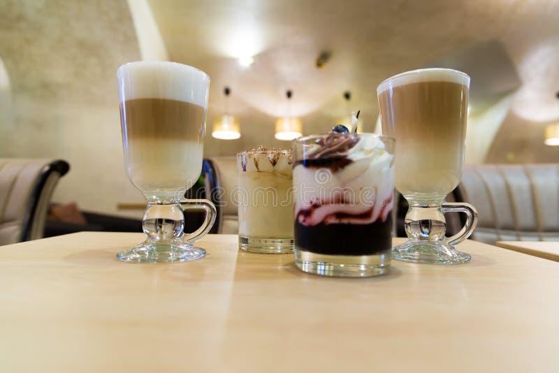 Kaffeelatte und -nachtisch mit Schlagsahne auf Tabelle in einem Café stockbild