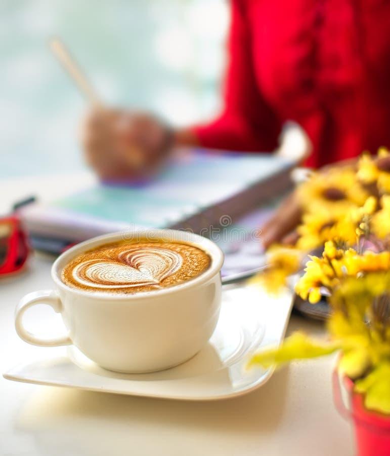 KaffeelLatte Art mit Blur gelb Blüte vorne und Rotes Kleid auf Buchheber schreiben Selektiver Fokus stockbilder