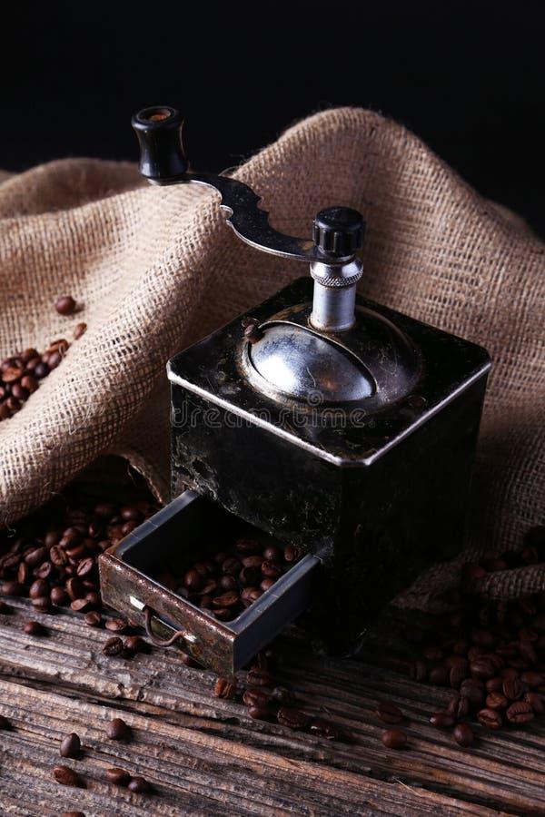 Kaffeemühle mit Kaffeebohnen auf braunem hölzernem Hintergrund lizenzfreies stockbild