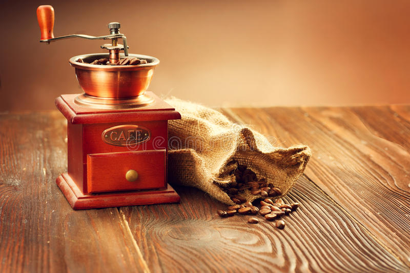 Kaffeemühle mit Leinwandsack voll Röstkaffeebohnen stockfoto