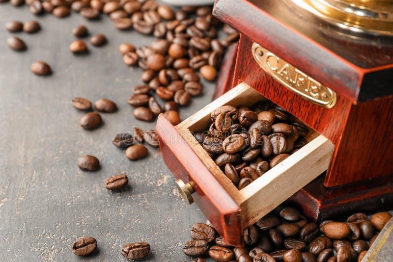 Kaffeemühle und Bohnen auf grauer Tabelle, Nahaufnahme stockbild