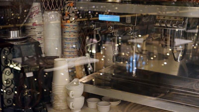 Kaffeemaschinen- und -plastikschalen als Teil des Kaffeestubeinnenraums stockfotografie