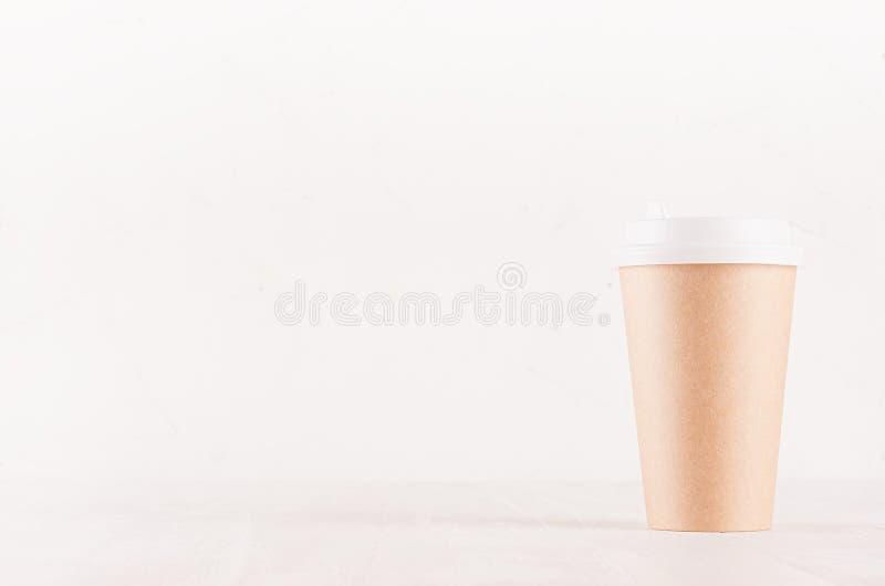 Kaffeemballagemodell - kraft brun pappers- kopp med det vita locket på det vita träbrädet med kopieringsutrymme, coffee shopinre royaltyfri bild