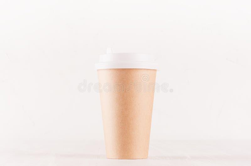 Kaffeemballagemodell - stor kraft brun pappers- kopp med det vita locket på det vita träbrädet, coffee shopinre arkivbilder