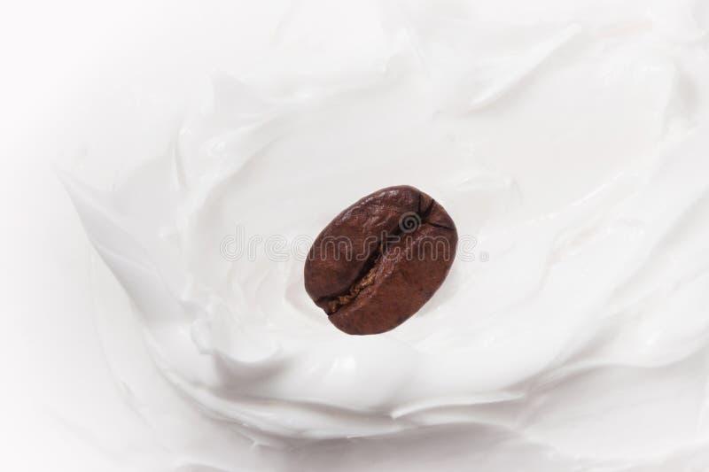Kaffeemilchnachtisch Kaffeebohnen unter Jogurt oder Milch Abschluss oben stockfotos