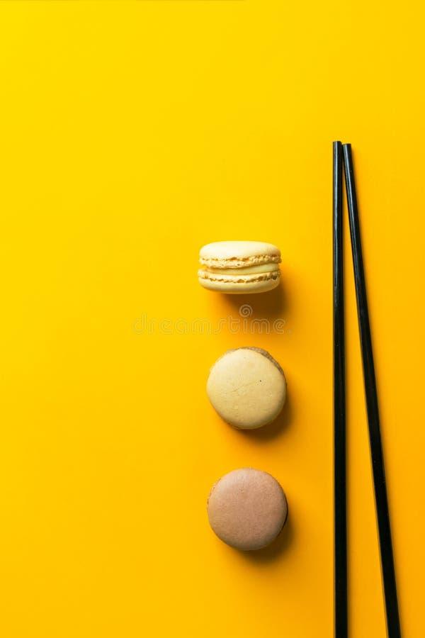 Kaffeemokka-Karamell macarons ausgebreitet in der vertikalen Reihe auf hellem gelbem Hintergrund mit schwarzen Essstäbchen Kreati lizenzfreies stockbild