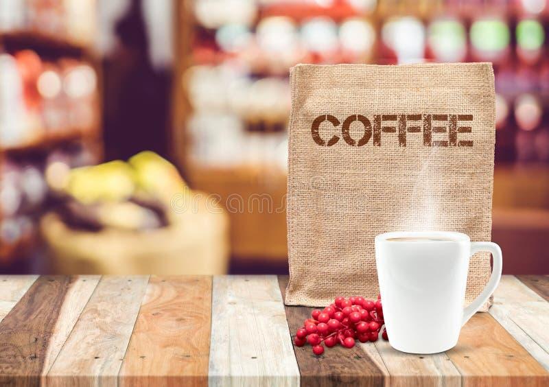 Kaffeesacktasche mit Kaffeetasse und Rauch mit Unschärfecafé backgro lizenzfreies stockbild