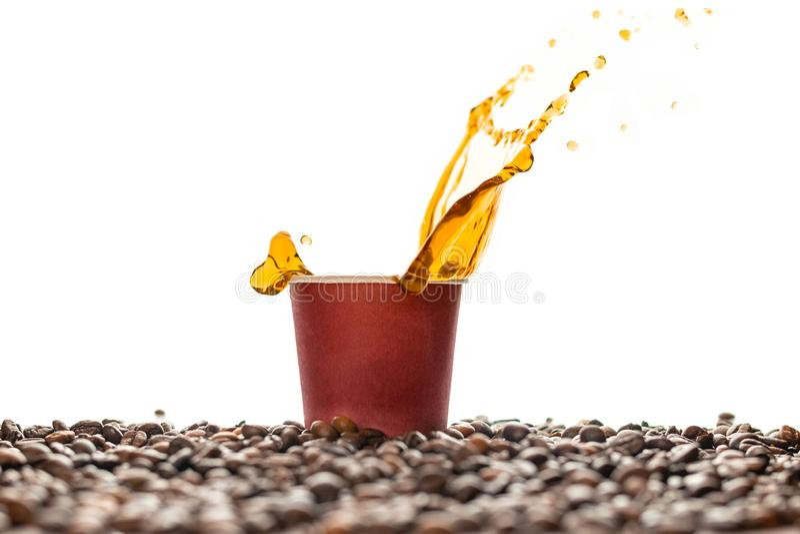 Kaffeespritzen in der braunen Wegwerfpapierschale mit den Kaffeebohnen lokalisiert auf Weiß stockfoto