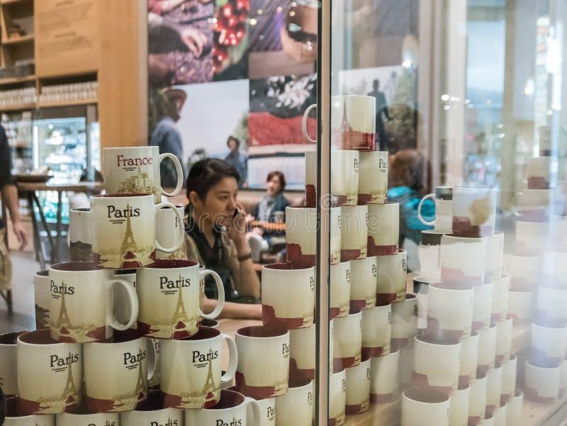 Kaffeestubekunde am Telefon sah durch Stapel souveni flüchtig stockfotos