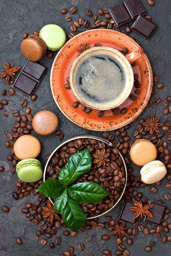 Kaffeetasse, Bohnen, Makronen und Schokolade auf Tabelle lizenzfreies stockfoto