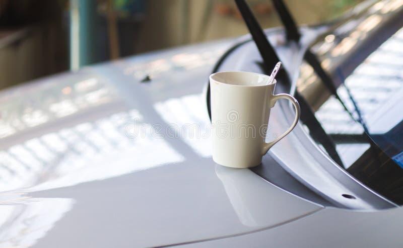 Kaffeetasse gesetzt auf Front des Autos lizenzfreie stockbilder