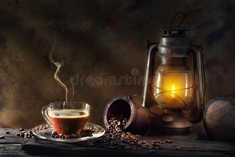 Kaffeetasse-Glas- und Weinlesekerosinlampenpetroleumlaterne, die w brennt stockbilder