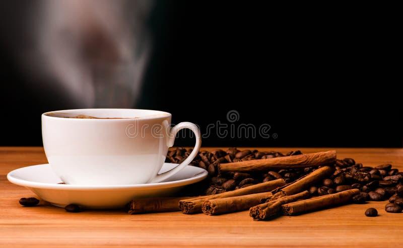 Kaffeetasse, Kaffeebohnen und Zimtstangen auf dunklem Hintergrund stockbilder
