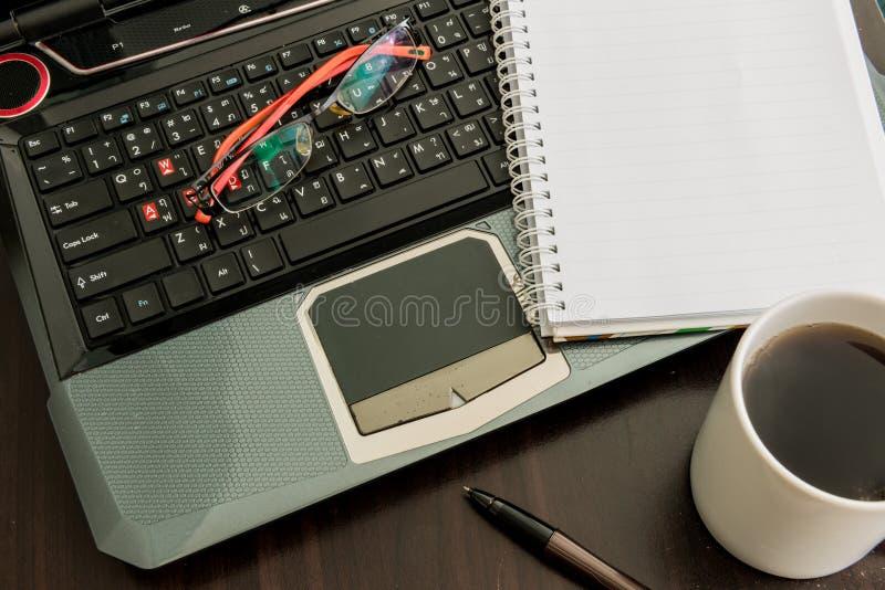 Kaffeetasse, Laptop, Stift, Notizblock und Gläser auf Holztisch lizenzfreies stockfoto
