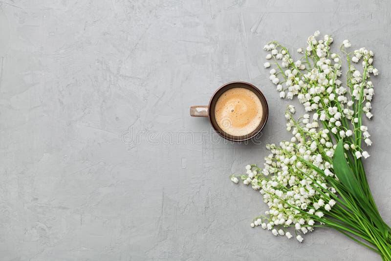 Kaffeetasse mit Blumenstrauß des Blumenmaiglöckchens auf grauer Steintischplatteansicht in Ebenenlage und in minimalistic Art lizenzfreie stockfotos