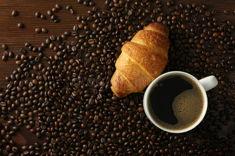 Kaffeetasse mit croisant lizenzfreie stockfotografie