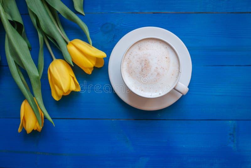 Kaffeetasse mit gelben Tulpenblumen lizenzfreies stockfoto