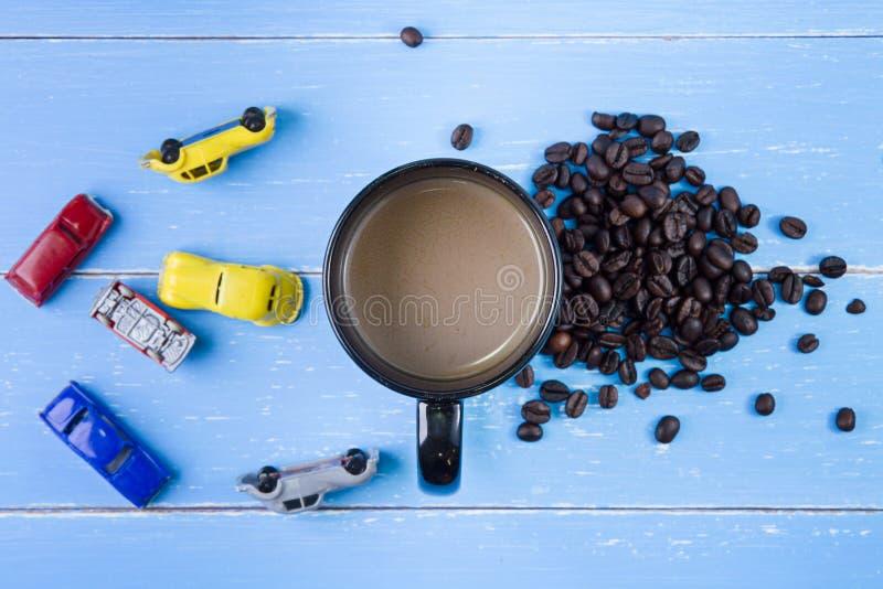 Kaffeetasse mit Kaffeebohne- und Spielwarenauto auf dem blauen hölzernen BAC stockbild