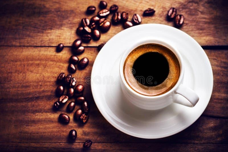 Kaffeetasse mit Kaffeebohnen auf hölzernem Hintergrund mit copyspac lizenzfreie stockfotografie