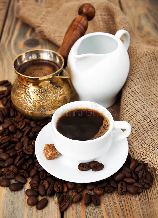 Kaffeetasse mit Kaffeebohnen, Milchkrug und Türken lizenzfreie stockbilder