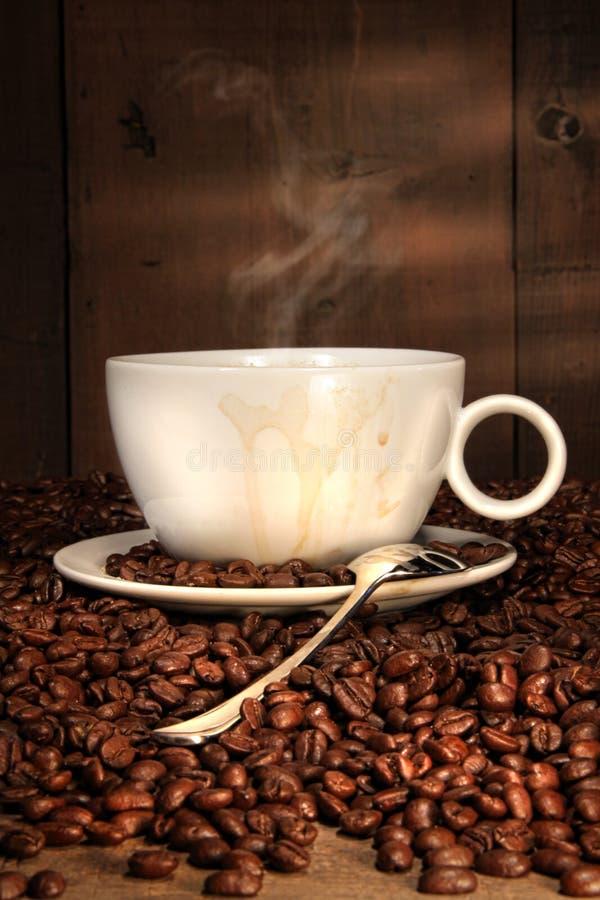 Kaffeetasse mit Löffel auf gebratenen Bohnen lizenzfreies stockfoto