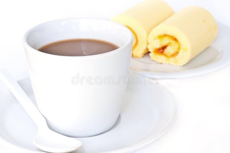 Kaffeetasse mit orange Kuchenrolle. lizenzfreie stockbilder