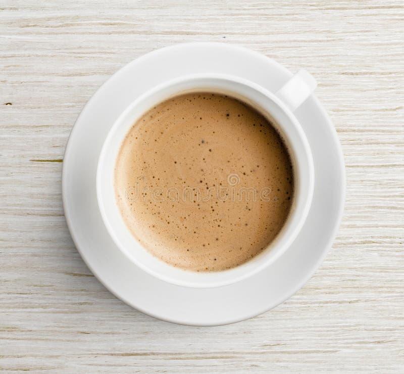 Kaffeetasse mit Schaum auf Draufsicht des Holztischs lizenzfreies stockfoto