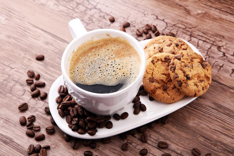 Kaffeetasse mit Schokoladenplätzchen und Kaffeebohnen auf hölzernem BAC lizenzfreie stockbilder