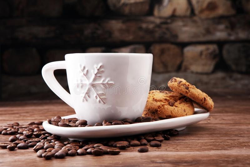 Kaffeetasse mit Schokoladenplätzchen und Kaffeebohnen auf hölzernem BAC stockbild