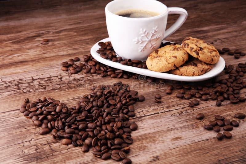 Kaffeetasse mit Schokoladenplätzchen und Kaffeebohnen auf hölzernem BAC lizenzfreies stockfoto