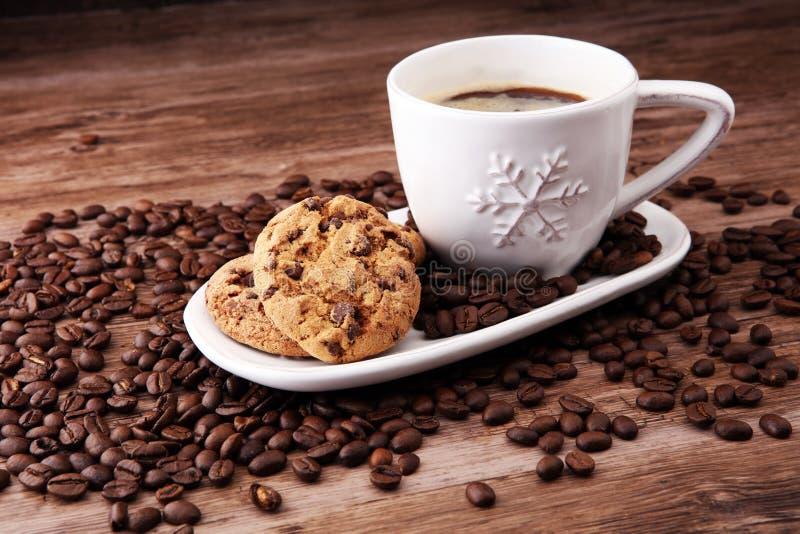 Kaffeetasse mit Schokoladenplätzchen und Kaffeebohnen auf hölzernem BAC stockfotografie