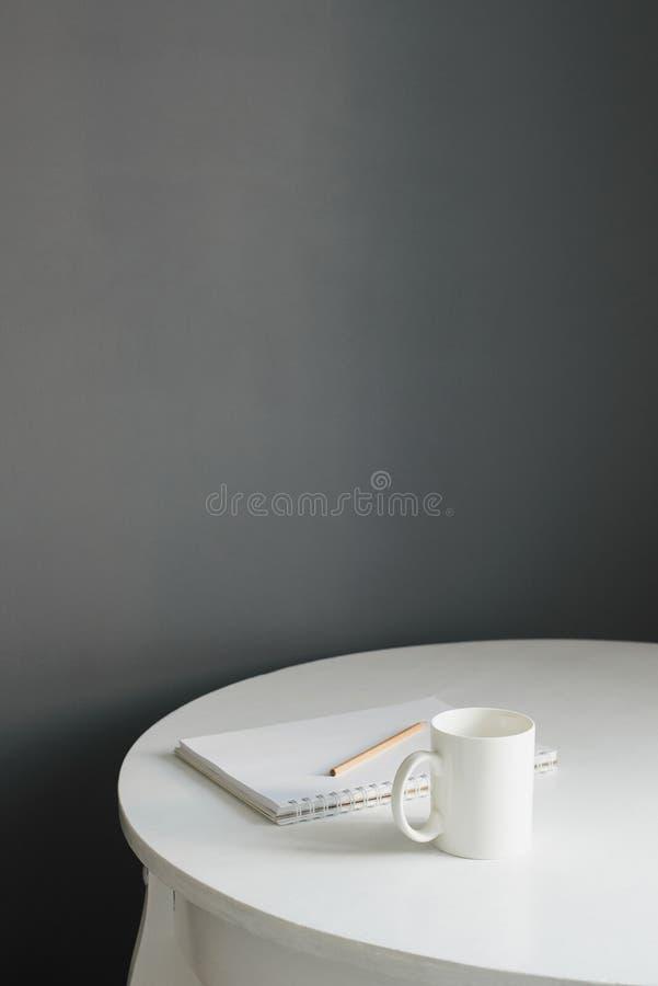 Kaffeetasse mit Sketchpad und Bleistift auf weißem Holztisch stockfotografie