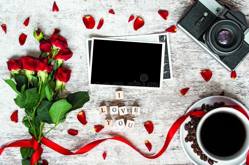 Kaffeetasse, Retro- Kamera der Weinlese mit Fotorahmen, rote Rosen und ich liebe dich Aufschrift stockfoto