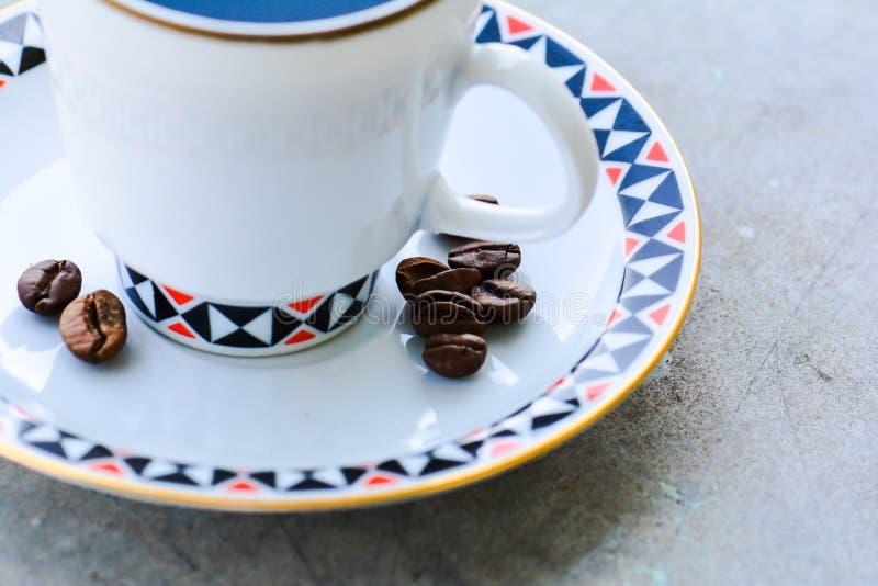 Kaffeetasse und Bohnen auf Untertasse lizenzfreie stockfotos