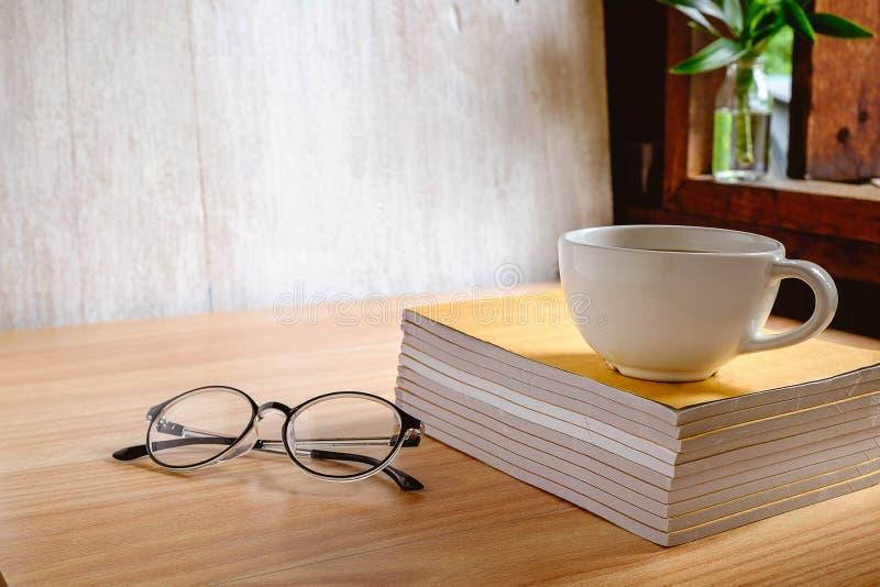 Kaffeetasse und Buch mit Gläsern lizenzfreie stockfotografie