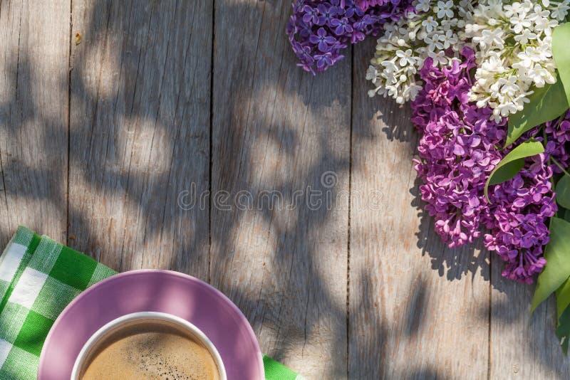 Kaffeetasse und bunte lila Blumen auf Gartentisch lizenzfreies stockbild