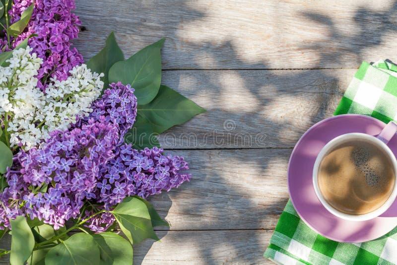 Kaffeetasse und bunte lila Blumen auf Gartentisch lizenzfreie stockfotos