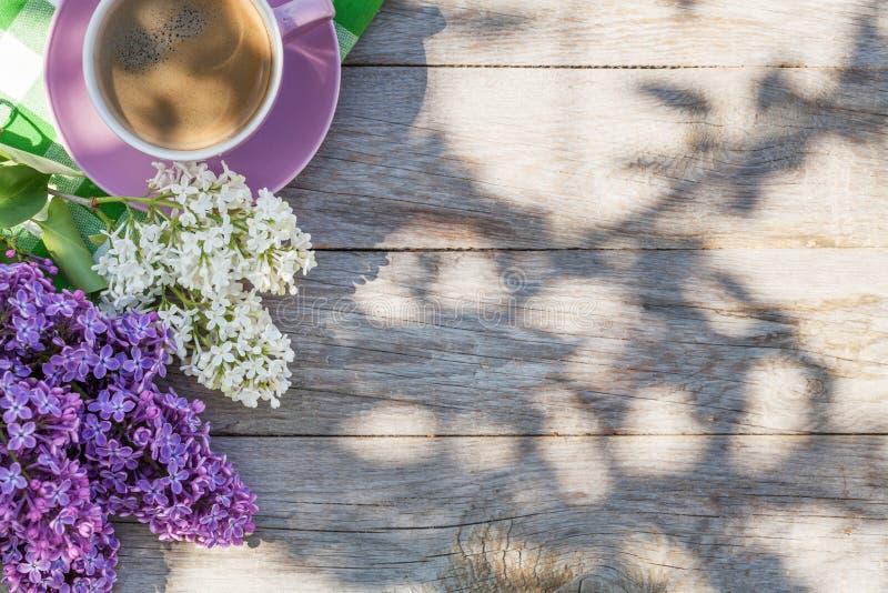 Kaffeetasse und bunte lila Blumen auf Gartentisch lizenzfreie stockbilder