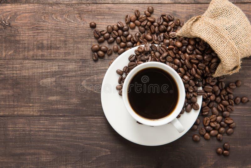 Kaffeetasse und Kaffeebohnen auf hölzernem Hintergrund Beschneidungspfad eingeschlossen lizenzfreies stockbild