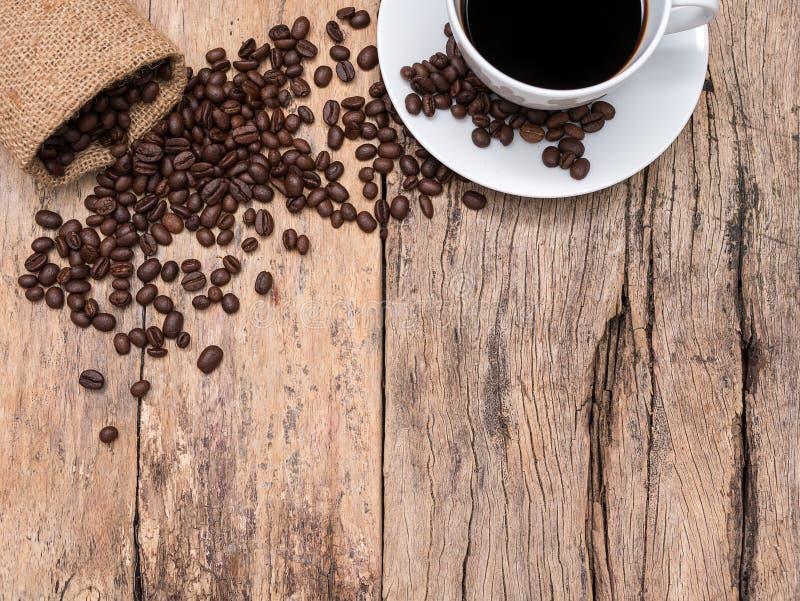 Kaffeetasse und Kaffeebohnen auf hölzernem Hintergrund mit Kopienraum stockfoto