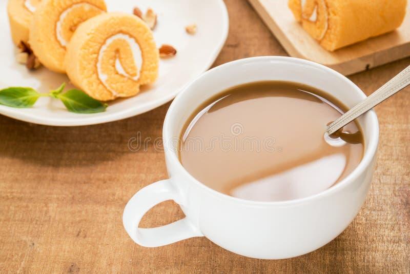 Kaffeetasse und orange Rollenkuchen stockbild