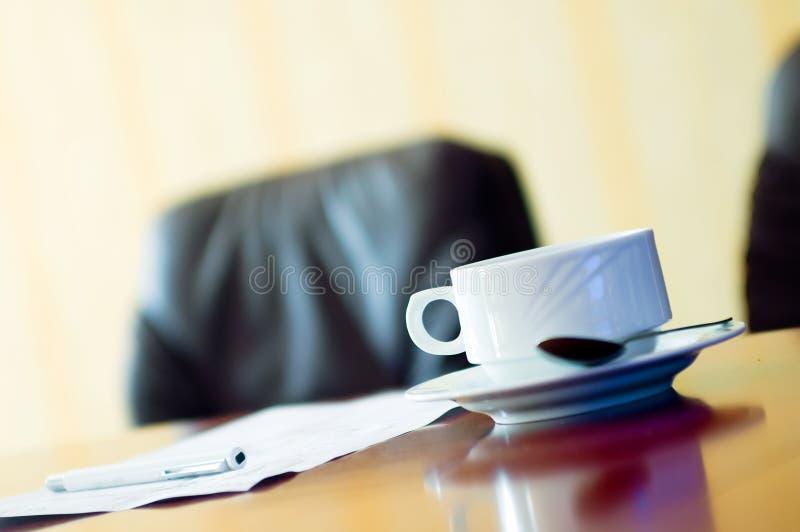 Kaffeetasse und Papiere im confe lizenzfreies stockfoto