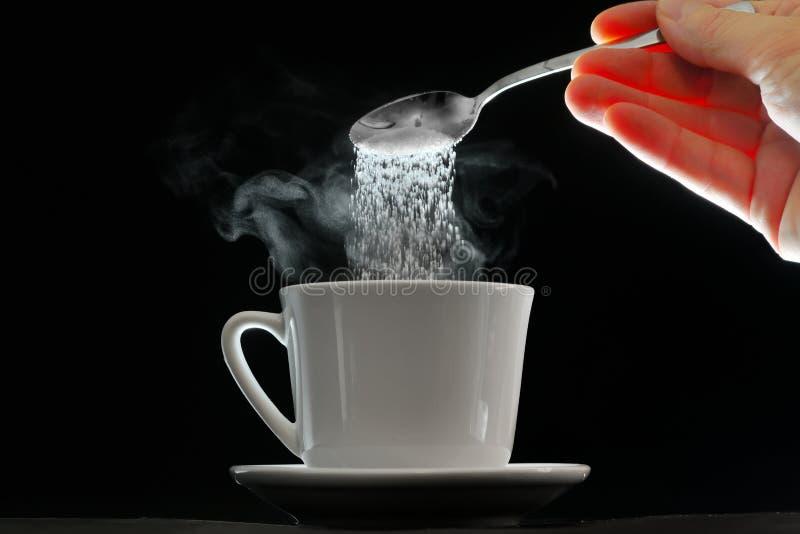 Kaffeetasse und strömender Zuckerlöffel lizenzfreie stockfotografie