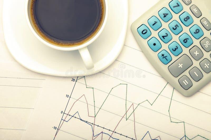 Kaffeetasse und Taschenrechner über Börsediagrammen - Ansicht von der Spitze Gefiltertes Bild: Kreuz verarbeiteter Weinleseeffekt lizenzfreies stockbild