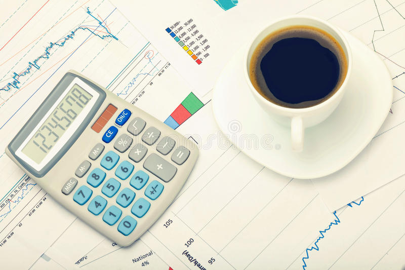 Kaffeetasse und Taschenrechner über Weltkarte und Finanzdiagrammen Gefiltertes Bild: Kreuz verarbeiteter Weinleseeffekt stockfotografie