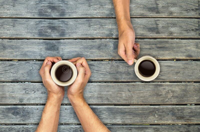 Kaffeetassehände, die an hölzerne Tabelle halten stockbilder