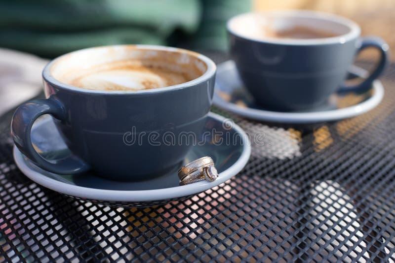 Kaffeetassen mit Eheringen stockbilder